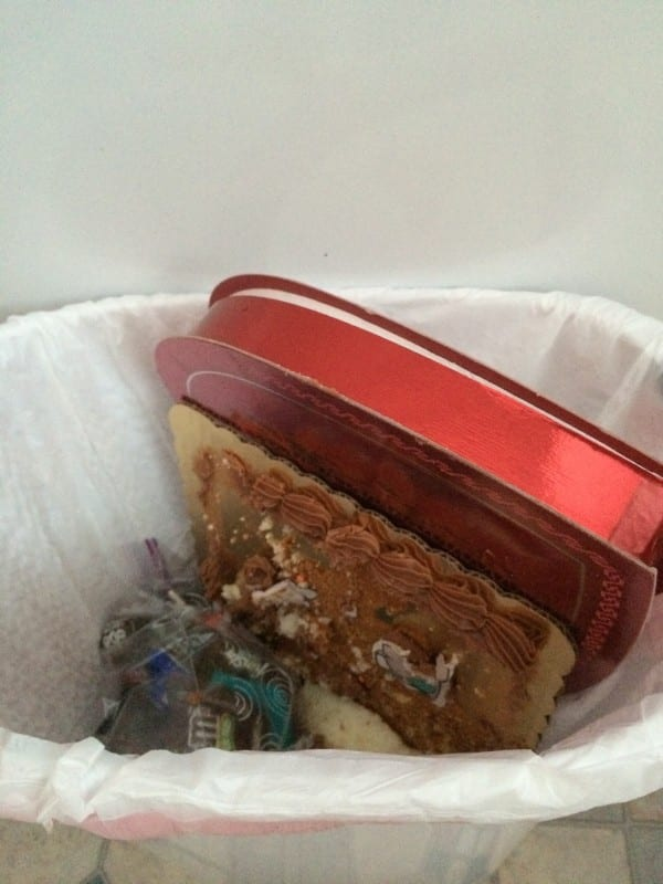 Valentine's Day chocolate in the garbage, image of red heart Valentine's Day candy in the trash bin,