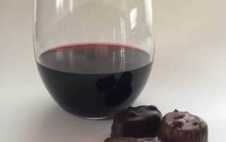 image of wine and chocolate, wine glass next to chocolate, red wine with three chocolates, stemless wine glass with red wine, stemless wine glass